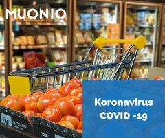 Ostoskärryt elintarvikeliikkeessä, kuvan päällä COVID -19 logo.